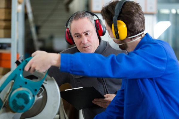 workers wearing earmuffs using circular saw
